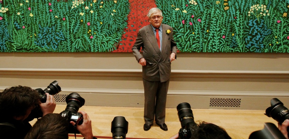 David Hockney poses in front of a detail of his painting The Arrival of Spring in Woldgate, East Yorkshire. (Reuters)